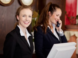 Two young attractive women working as professional receptionists at a hotel